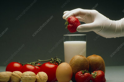 Gloved hand with food that can cause allergies