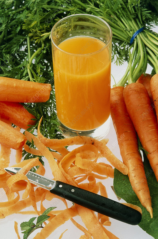 Glass of carrot juice surrounded by carrots