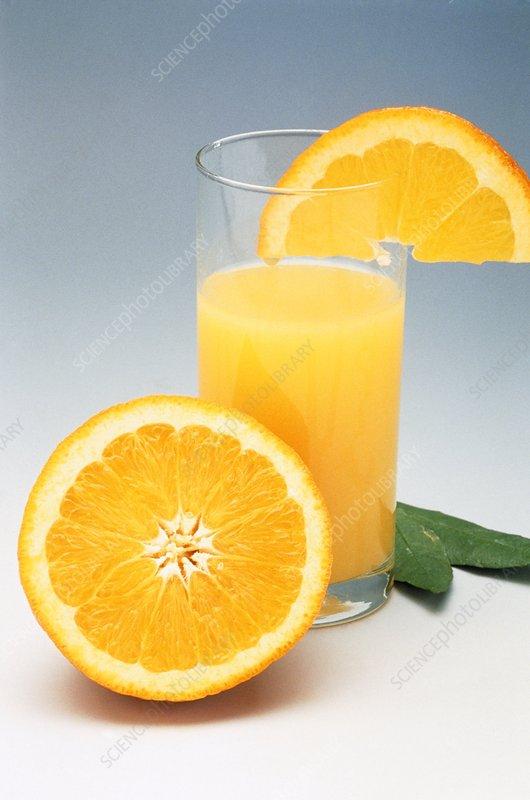 Glass of orange juice with halved orange