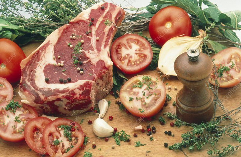 Raw red meat surrounded by herbs and vegetables