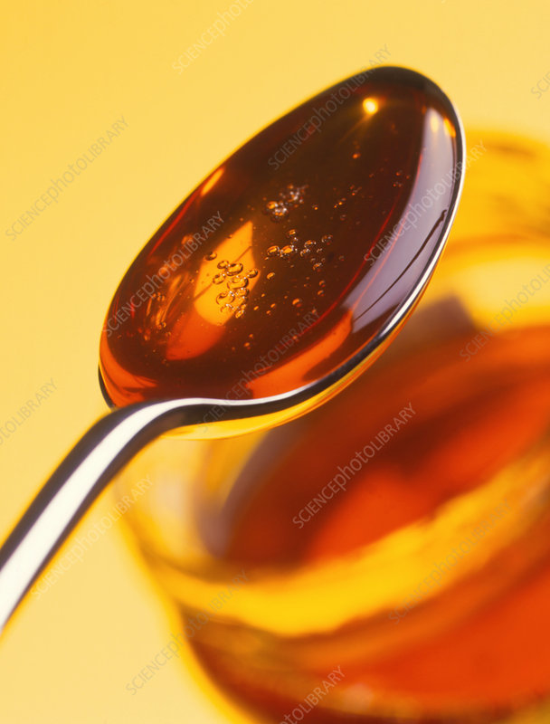 Spoonful of honey above a jar