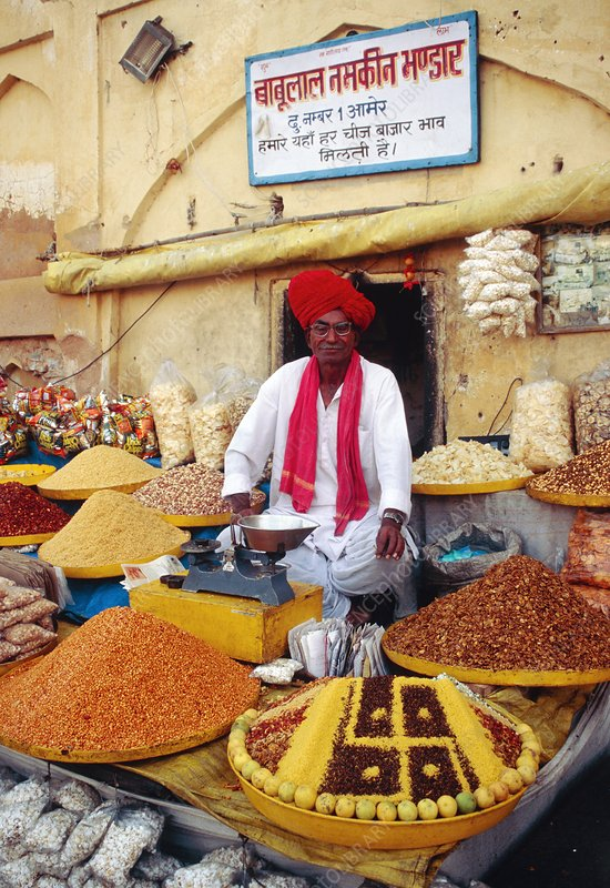 Indian spice seller sitting amongst spice baskets