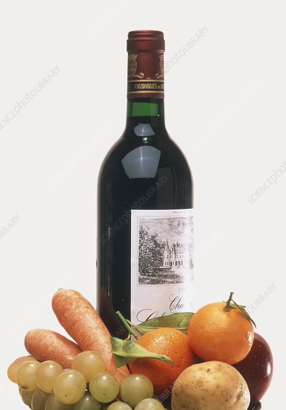 Bottle of red wine with fruit and vegetables