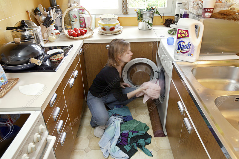 Woman loading a washing machine