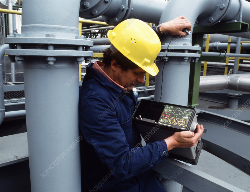 Technician using ultrasound to test pipe integrity