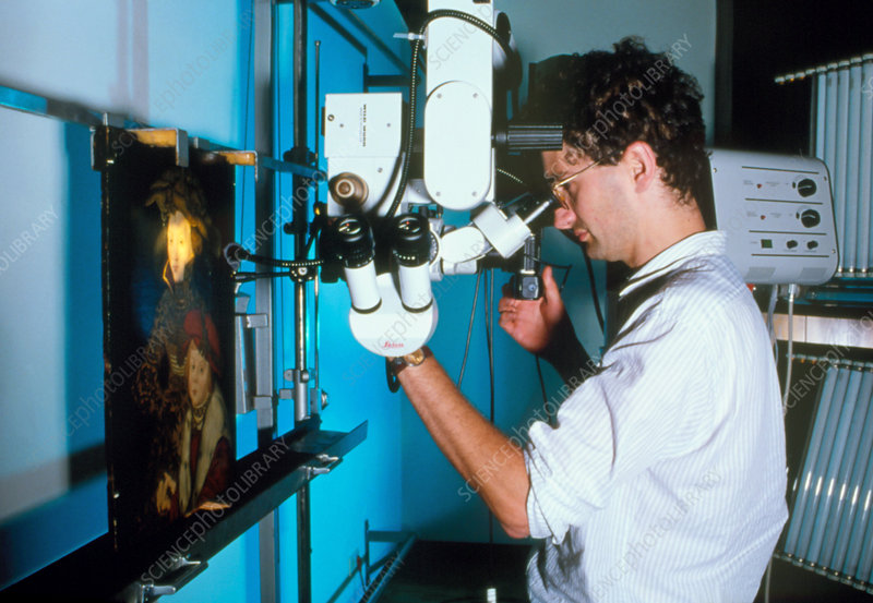 Technician examines forged painting by microscope