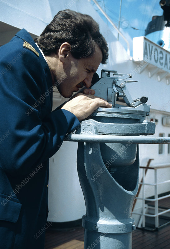 Ship's navigation officer takes a compass bearing