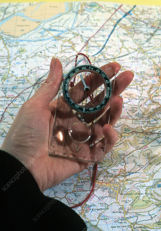 Person uses a magnetic compass and a map