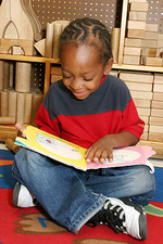 Boy Reads Book in Day Care