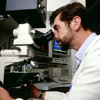 Cancer research scientist with confocal microscope