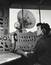 Technician operates satellite radar tracking dish