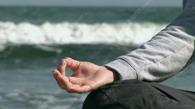 Woman meditating on the beach
