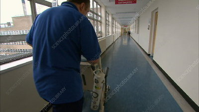 Orderly wheeling patient down corridor