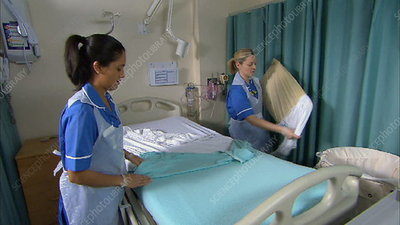 Nurses making hospital bed