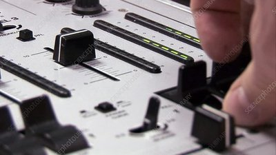 Adjusting faders on a sound board