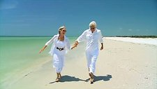 Elderly couple running on a beach