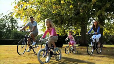 Family cycling on grass