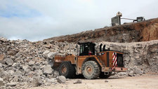 Excavator carrying rubble in a quarry