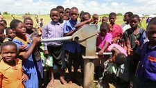 Children using a well pump, Malawi
