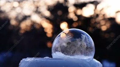 Ice crystals forming on a soap bubble