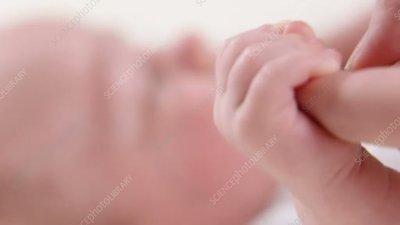 Baby grasping parent's finger