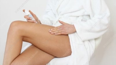 Woman applying moisturiser to leg