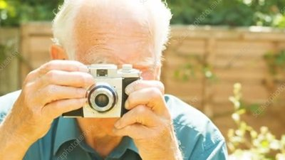 Elderly man taking pictures with camera