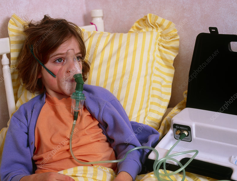 Young girl in bed using a nebulizer for asthma