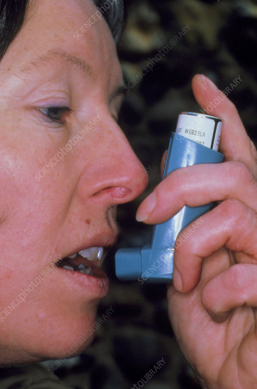 Woman using inhaler to control asthma.