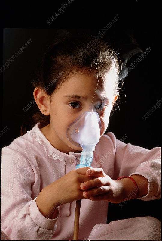 Asthmatic young girl breathes into a nebulizer