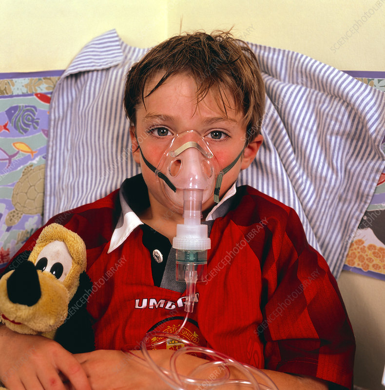 Asthmatic young boy breathes into a nebulizer