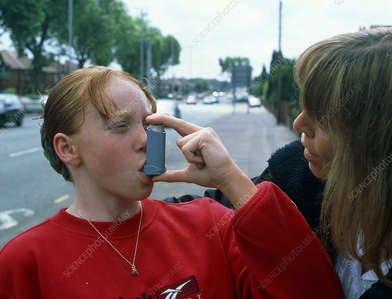 Girl uses an aerosol inhaler for asthma