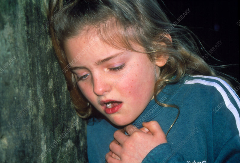 9 year old girl holding chest during asthma attack
