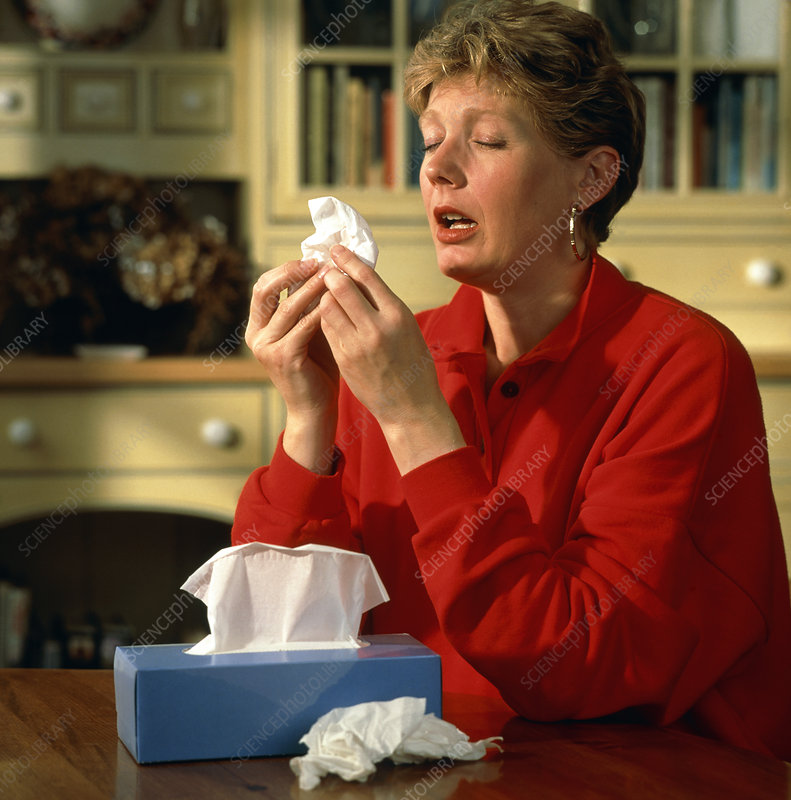 Rhinitis: woman sneezes into a tissue