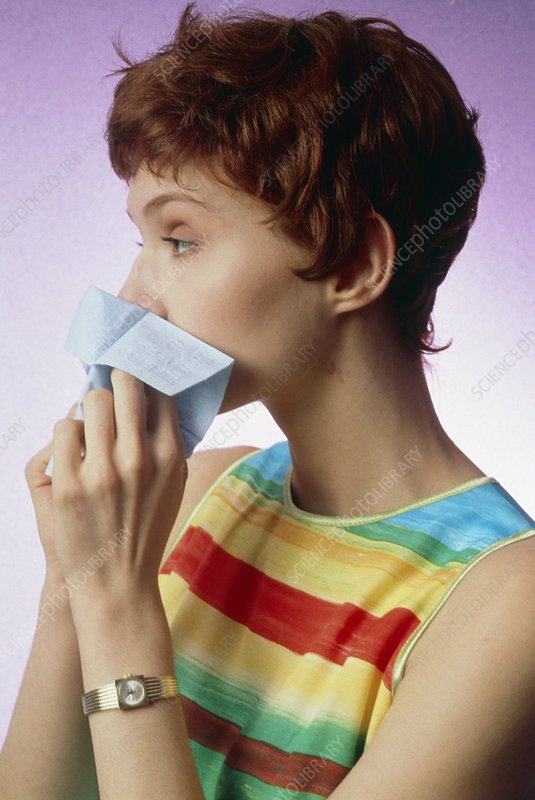 Woman blowing her nose suffering from rhinitis