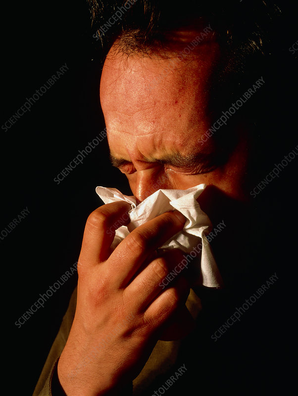 Man blowing his nose suffering from rhinitis