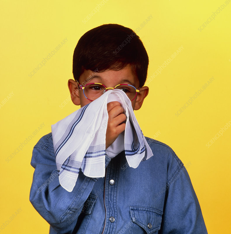 Young boy blowing his nose suffering from rhinitis