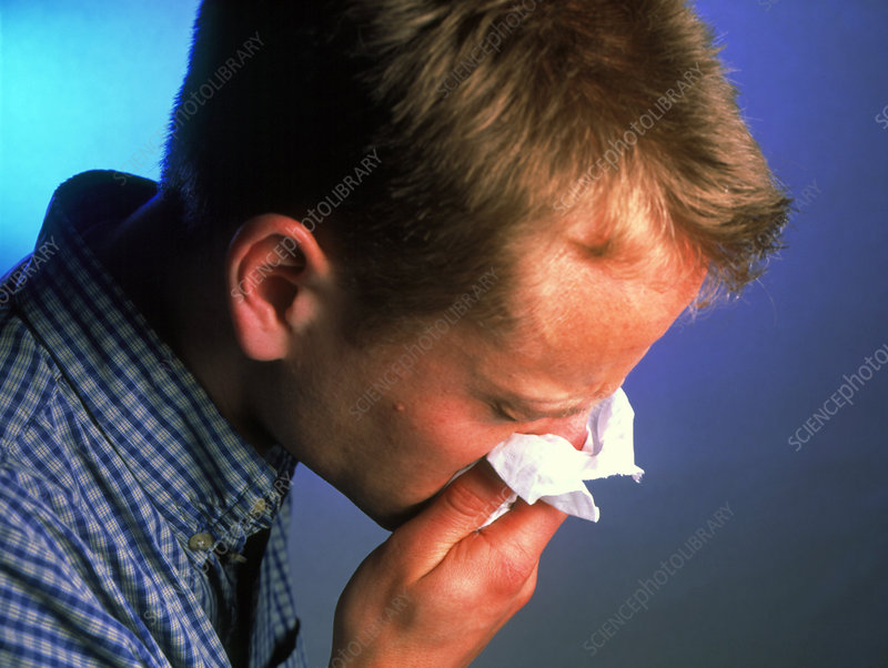 Young man with a cold blowing his nose