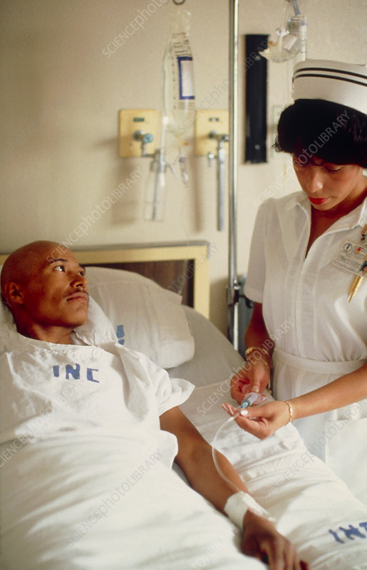 Nurse administering IV drug to cancer patient
