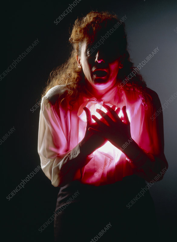 Woman holding her chest in angina or heart attack