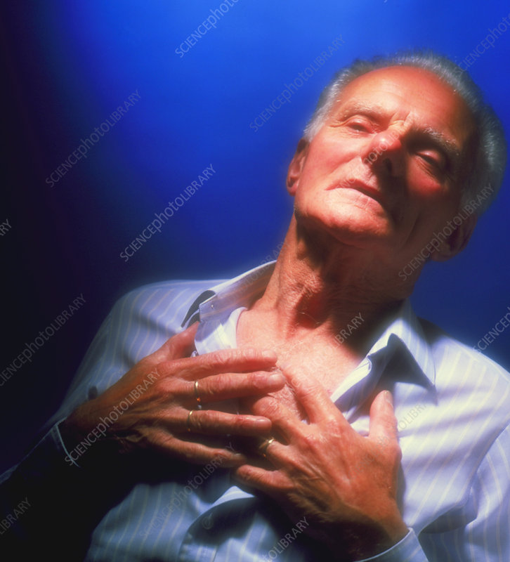 Man holds his chest due to angina or heart attack