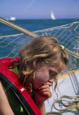 Young girl suffering from seasickness in a boat