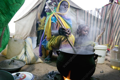 Refugee woman cooking food