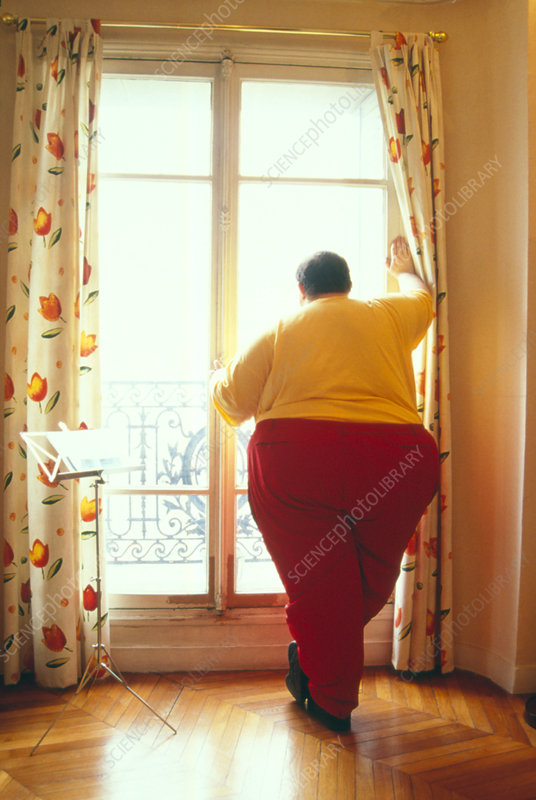 Obese man looking out of a window