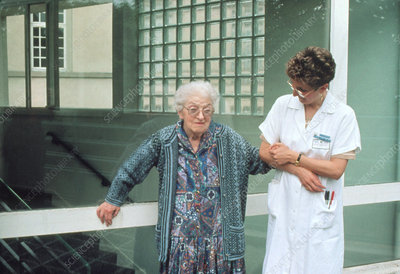 Elderly woman with Parkinson's disease, and nurse