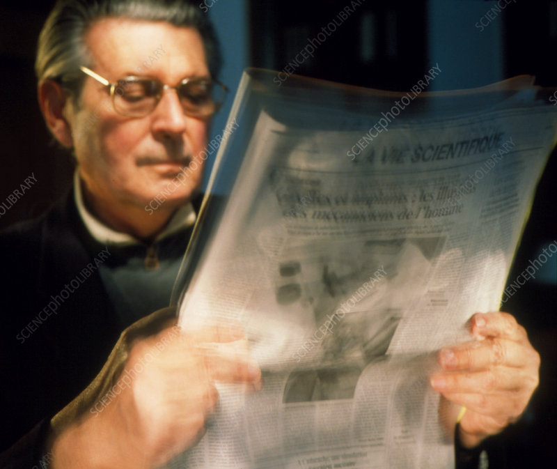 Man with Parkinson's disease reading a newspaper