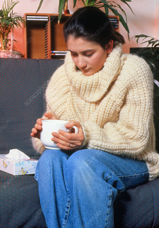 Depression: young woman with hot drink & tissues