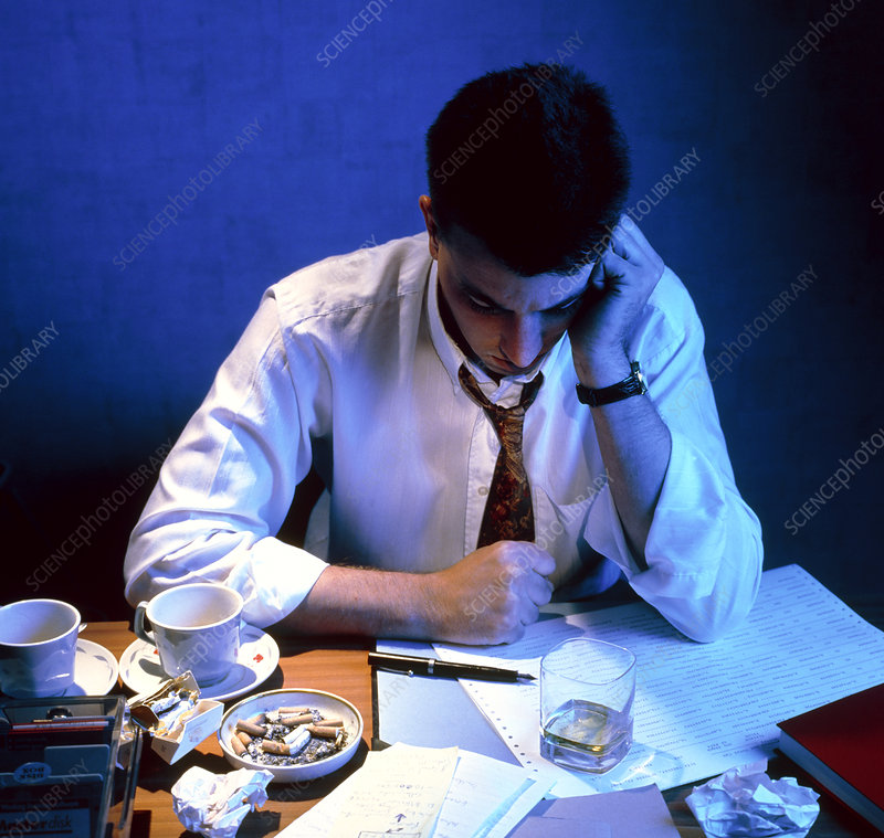 Fatigued businessman sitting at his desk at night