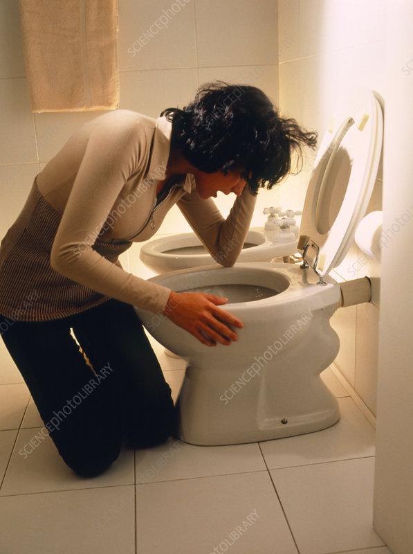 Bulimia: young woman trying to vomit at a toilet