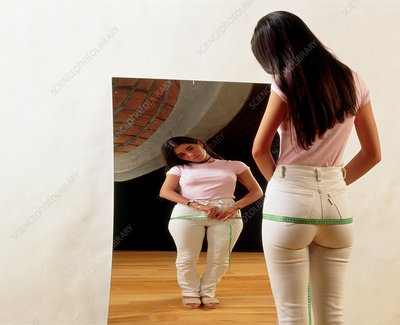 Anorexia nervosa: girl examines figure at mirror